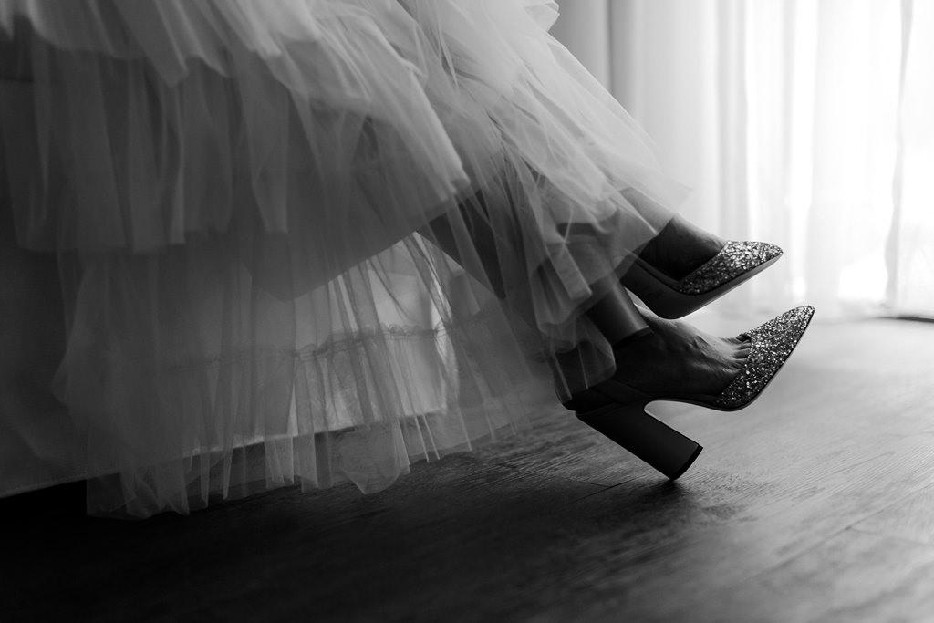 Hochzeitsfoto vom Brautkleidsaum und den Brautschuhen