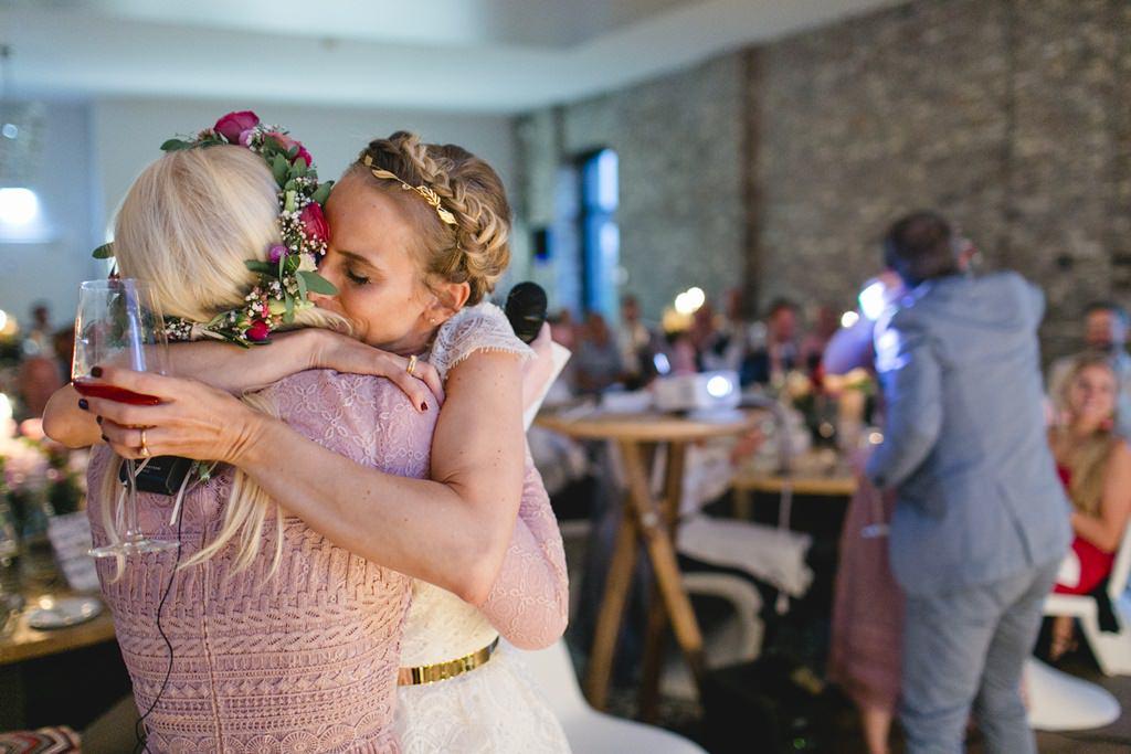 die Braut umarmt eine Freundin während der Hochzeitsfeier