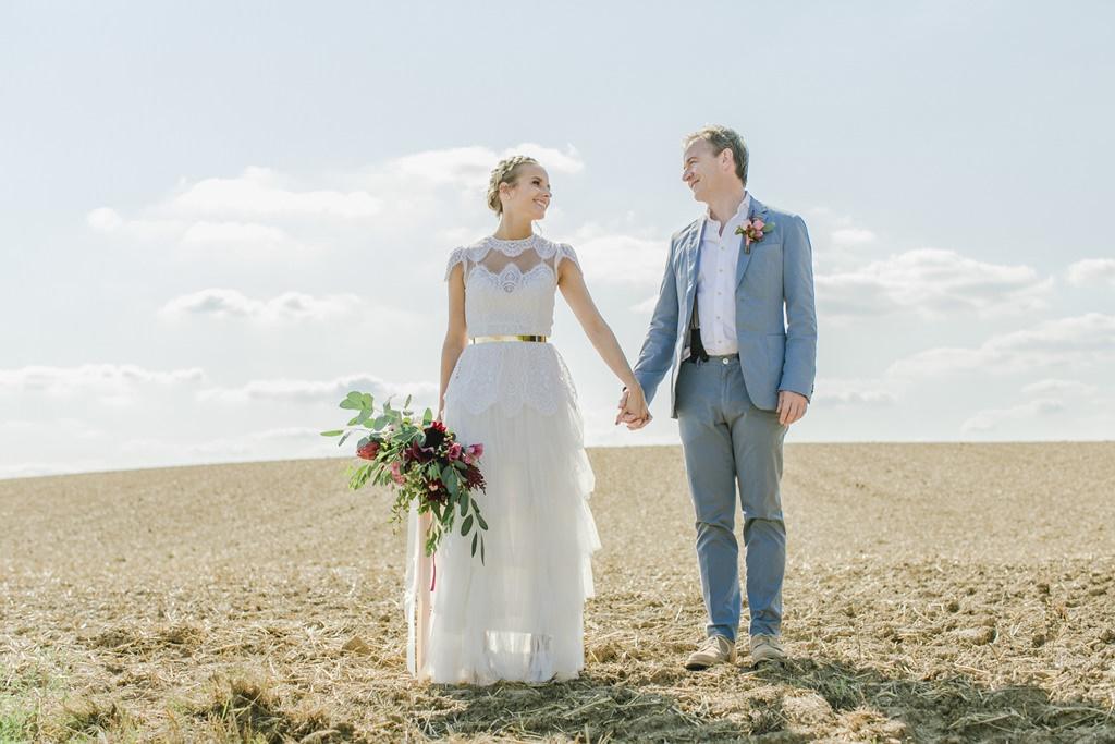 Braut und Bräutigam laufen Hand in Hand über ein Feld | fotografiert von Hanna Witte