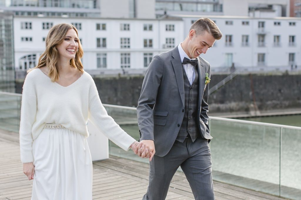 urbanes Hochzeitsfoto: Das Brautpaar läuft durch die Stadt