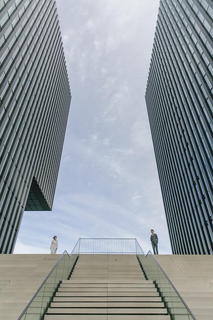 Hochzeitsfoto Idee: Das Brautpaar steht an einer langen Treppe zwischen 2 Hochhäusern
