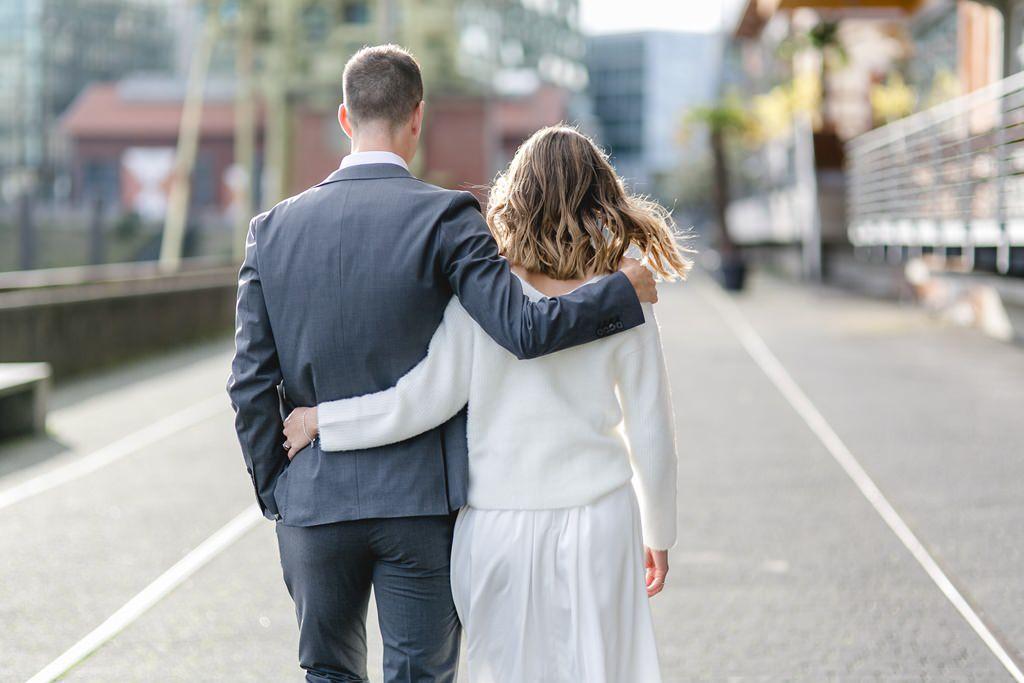 das Brautpaar Arm in Arm, von hinten fotografiert
