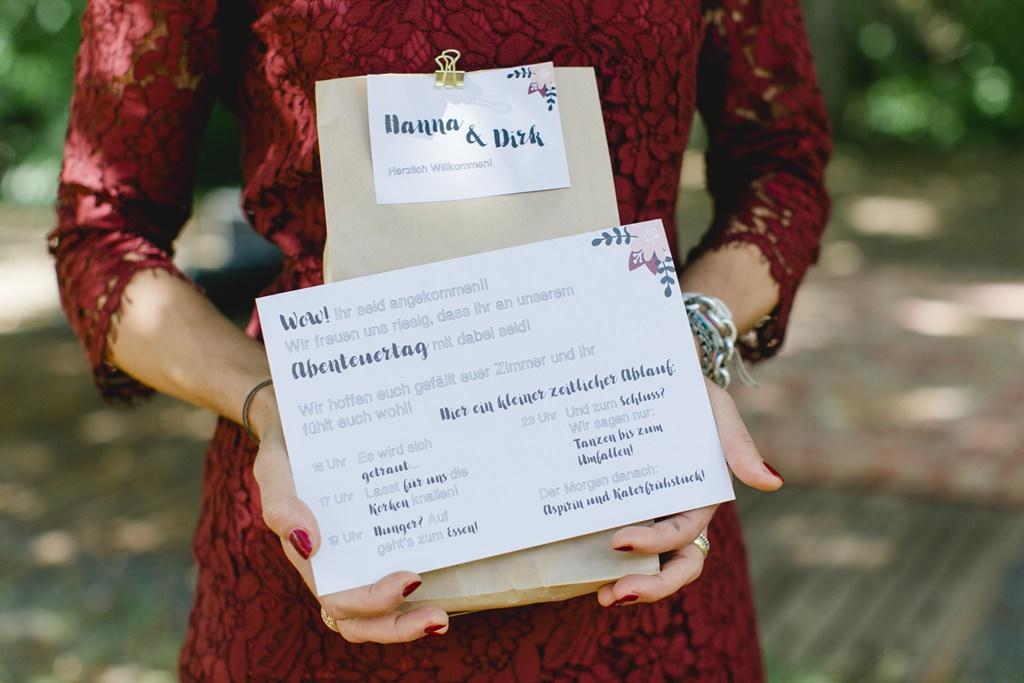 die Brautjungfer hält das Willkommensgeschenk des Brautpaares samt Ablaufplan in der Hand