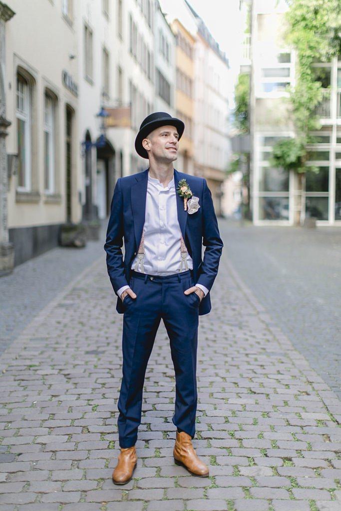 der Bräutigam in seinem lässigen dunkelblauen Anzug mit Hut und Hosenträgern | Foto: Hanna Witte