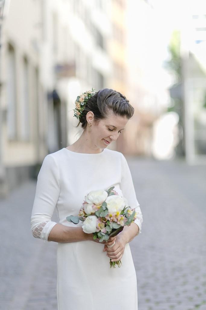 die Braut in ihrem schlichten, hochgeschlossenen Standesamt Brautkleid mit langen Ärmeln | Foto: Hanna Witte