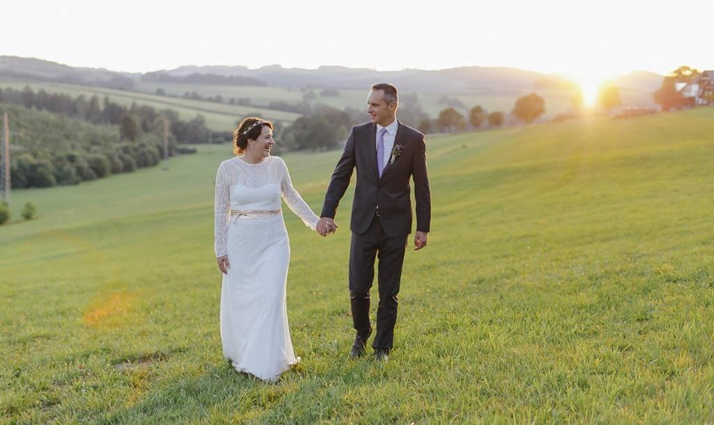 Hochzeitsfoto von Braut und Bräutigam auf einer Wiese bei Sonnenuntergang | Foto: Hanna Witte