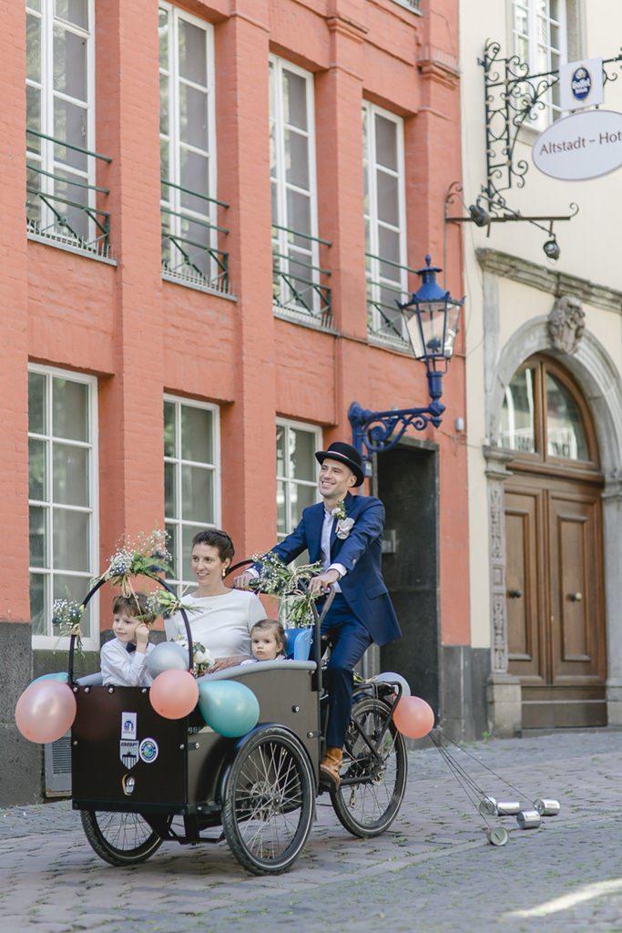 das Brautpaar fährt mit seinen Kindern in einem geschmückten Lastenfahrrad durch Köln | Foto: Hanna Witte