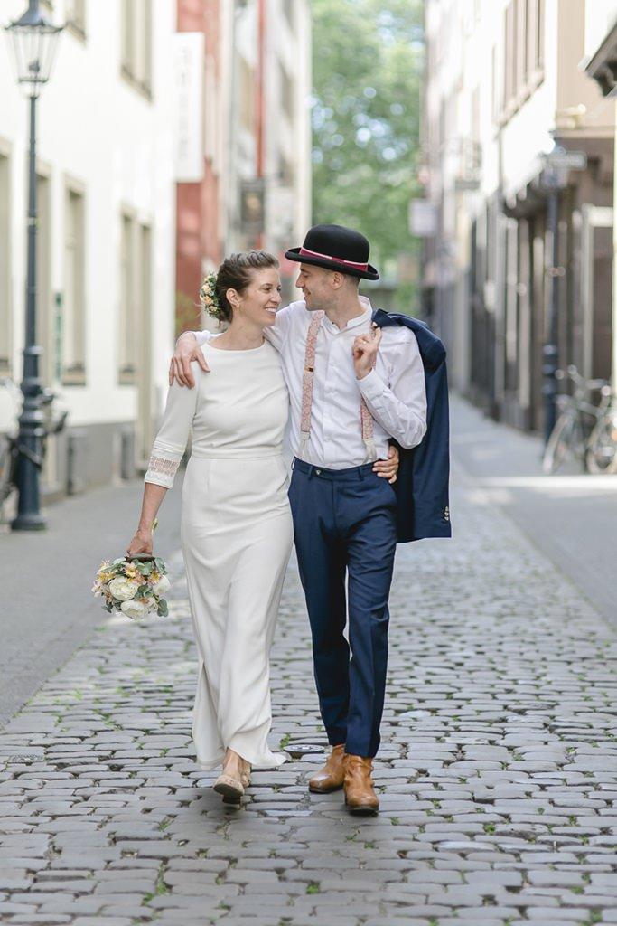 Braut und Bräutigam laufen Arm in Arm durch die Kölner Altstadt | Foto: Hanna Witte