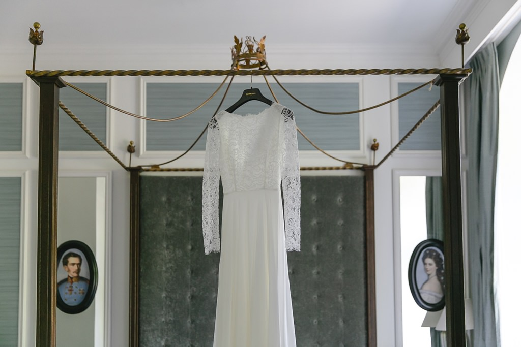 das Brautkleid mit Spitze und langen Ärmeln von Kaviar Gauche hängt am Bettrahmen   Foto: Hanna Witte