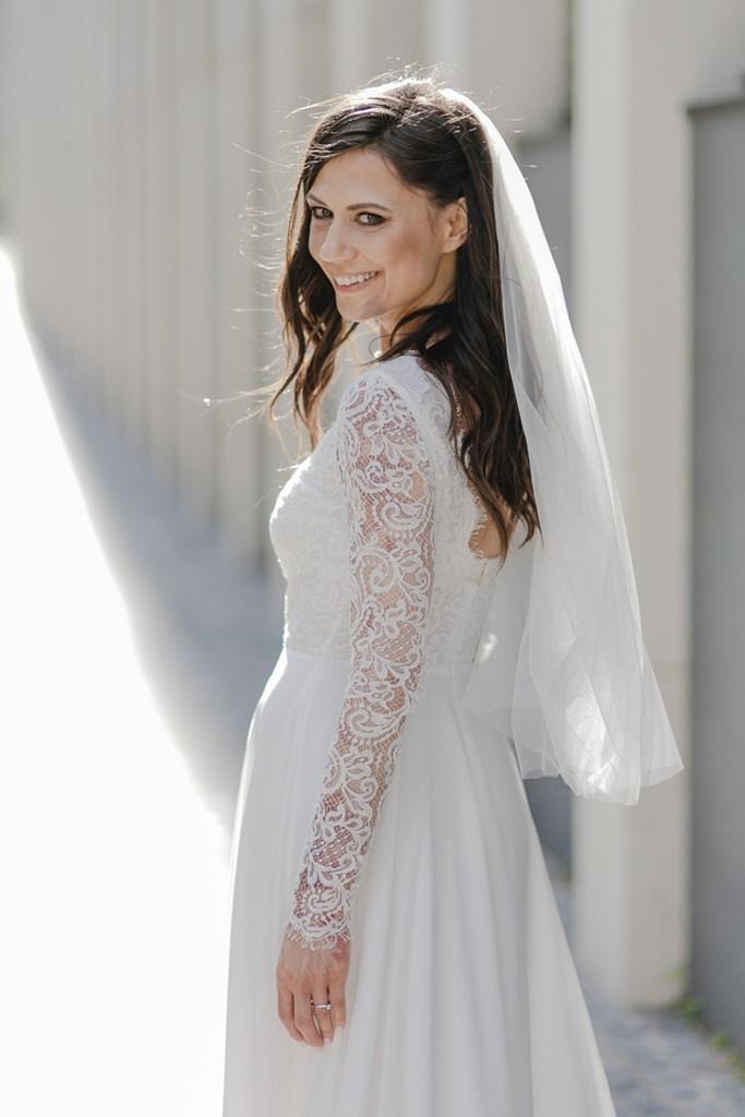 Braut mit Schleier und einem Brautkleid mit Spitze und langen Ärmeln von Kaviar Gauche   Foto: Hanna Witte