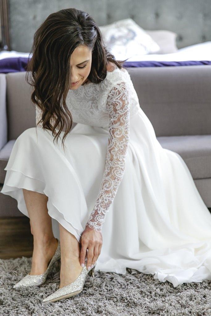 Hochzeitsfoto von der Braut beim Anziehen ihrer Jimmy Choo Brautschuhe   Foto: Hanna Witte