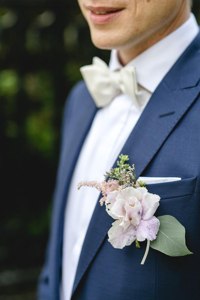 Hochzeitsfoto vom rosafarbenen Blumenanstecker am blauen Bräutigamanzug   Foto: Hanna Witte