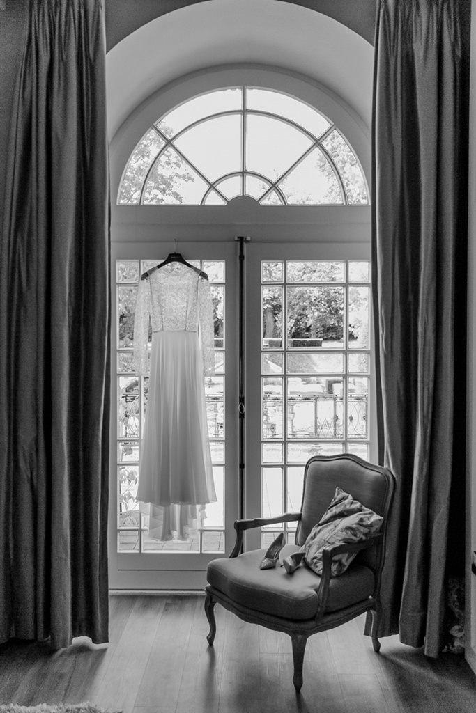 Hochzeitsfotoidee: Das Brautkleid hängt vor einem großen Fenster im Hotel Kasteel Bloemendal   Foto: Hanna Witte