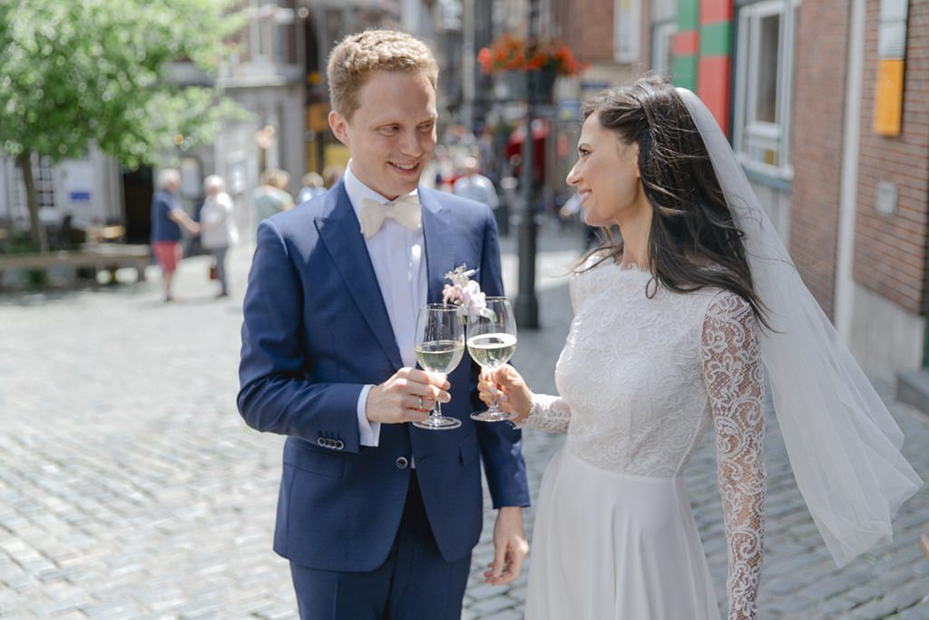 das Brautpaar stößt nach der Standesamt Hochzeit in Aachen mit einem Glas Sekt an   Foto: Hanna Witte