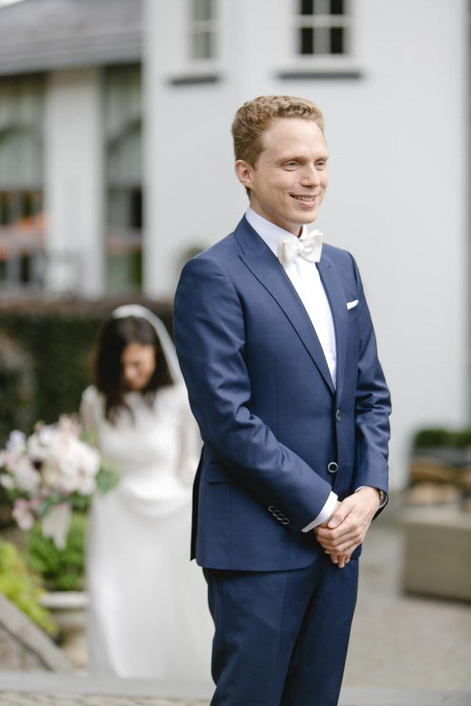 Hochzeitsfoto vom First Look: Die Braut schleicht sich von hinten an den Bräutigam heran   Foto: Hanna Witte