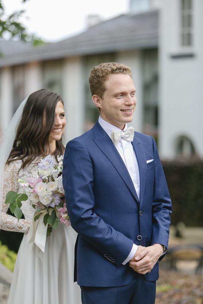 Hochzeitsfoto vom First Look: Die Braut steht hinter dem Bräutigam   Foto: Hanna Witte