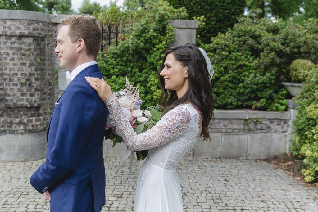 Hochzeitsfoto vom First Look: Die Braut fasst den Bräutigam an die Schulter   Foto: Hanna Witte