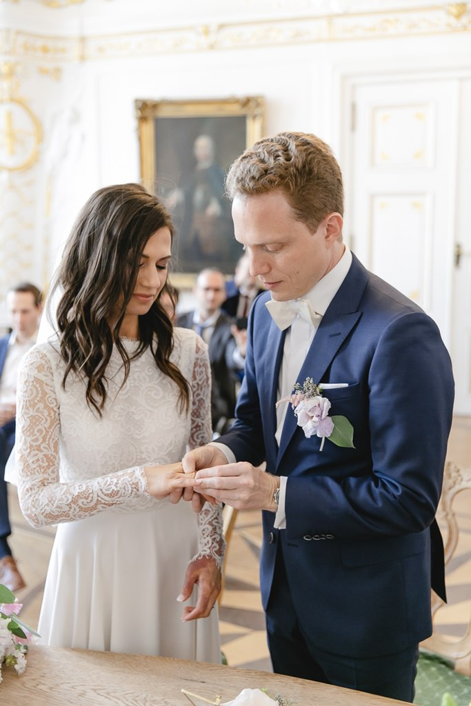 das Brautpaar beim Ringtausch während der Standesamt Hochzeit im weißen Saal im Rathaus Aachen   Foto: Hanna Witte