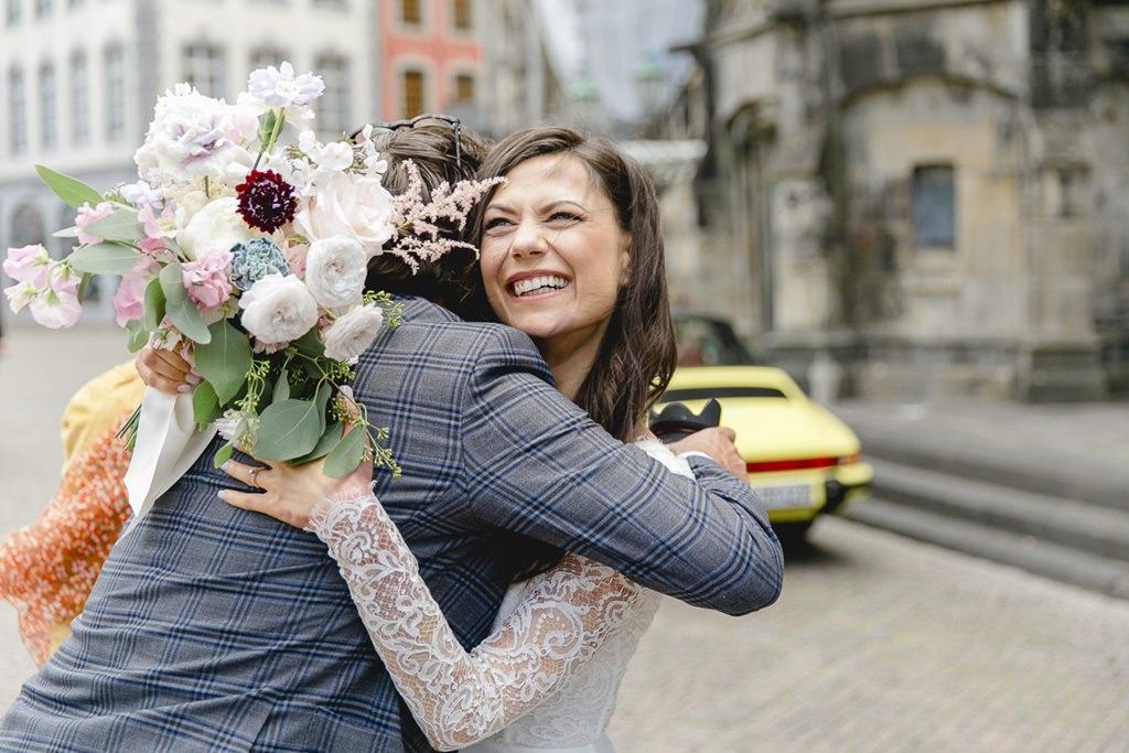 die Braut wird von einem Hochzeitsgast umarmt   Foto: Hanna Witte