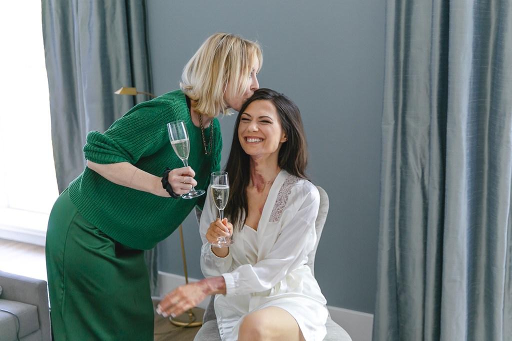 Hochzeitsfotoidee Getting Ready: Braut und Stylistin trinken zusammen ein Glas Sekt   Foto: Hanna Witte