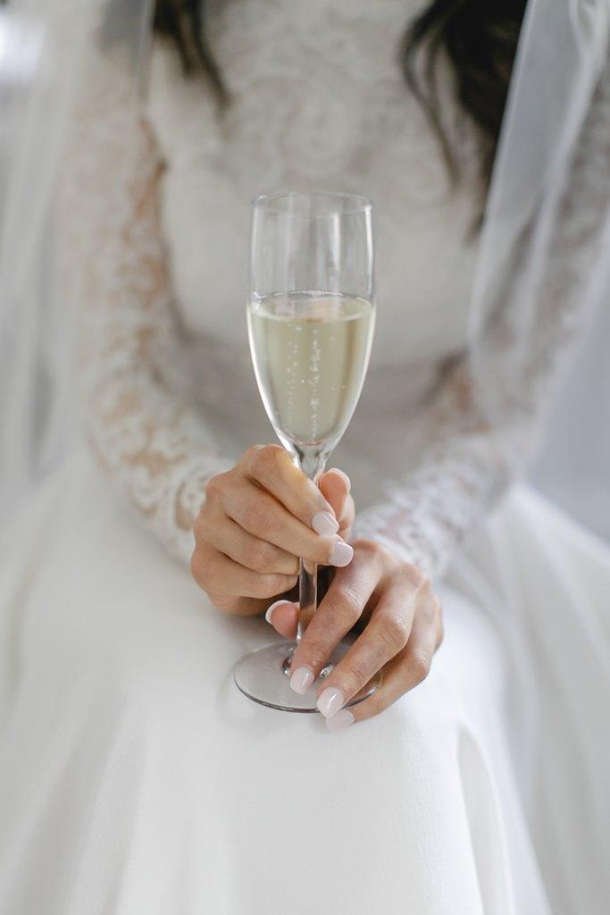 die Braut rinkt beim Getting Ready ein Glas Sekt   Foto: Hanna Witte