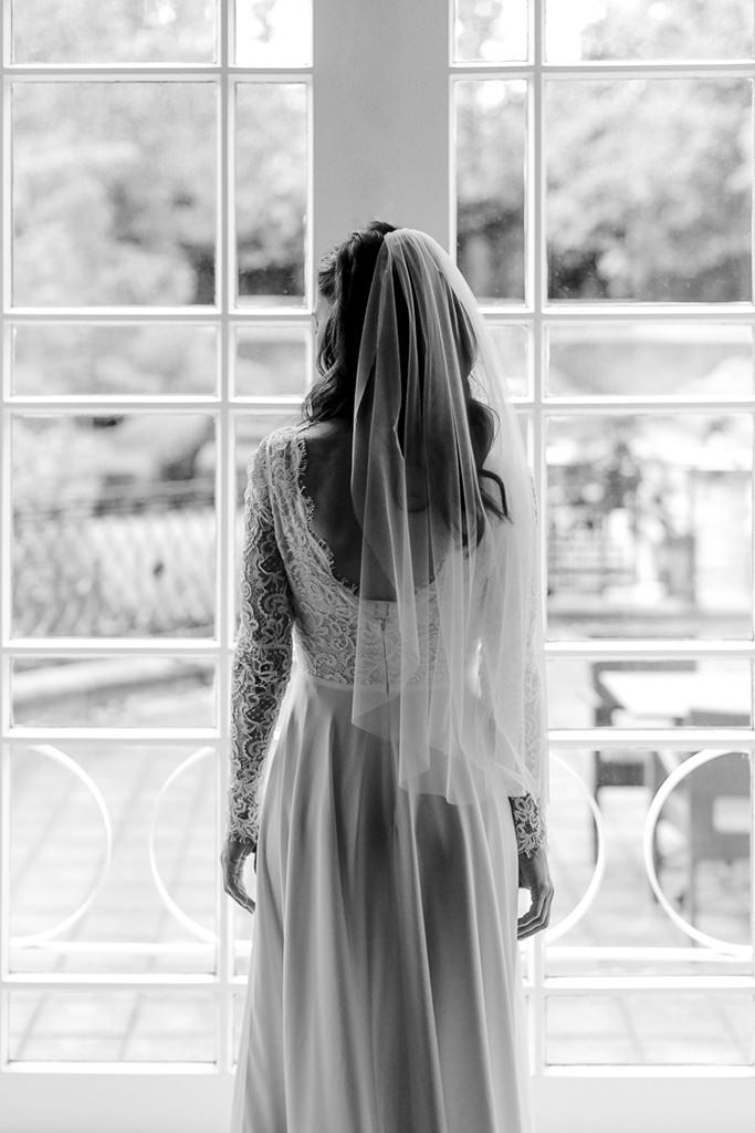 Rückenaufnahme der Braut mit Schleier vor einem großen Fenster   Foto: Hanna Witte