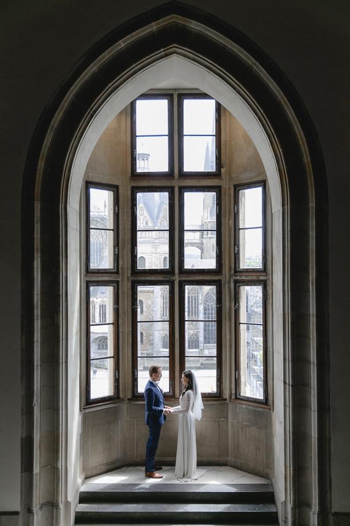 Hochzeitsfotoidee: Das Brautpaar steht unter einem großen Torbogen vor einer Fensterwand   Foto: Hanna Witte