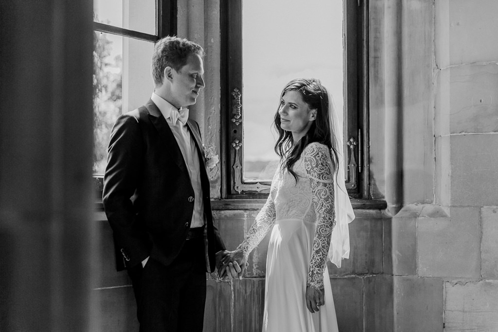 Braut und Bräutigam stehen verliebt Hand in Hand vor einem Fenster   Foto: Hanna Witte