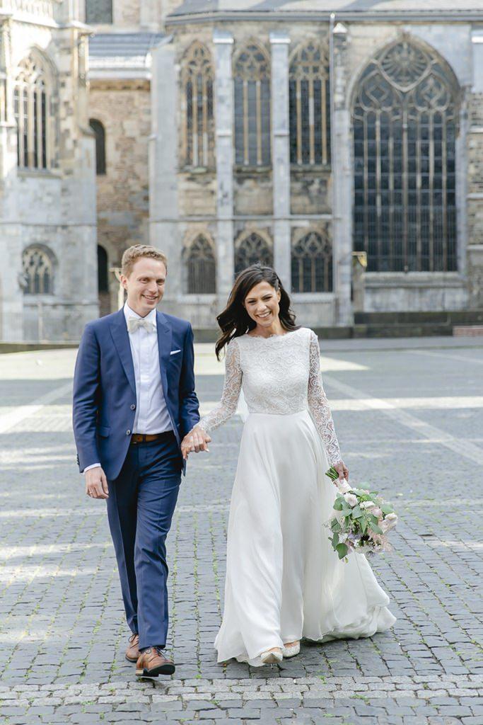 Braut und Bräutigam laufen über den Vorplatz des Aachener Doms   Foto: Hanna Witte