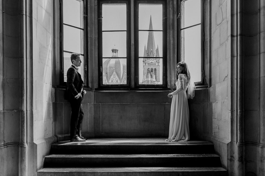 Cooles Hochzeitsfoto von Braut und Bräutigam, die lässig vor einem Fenster lehnen   Foto: Hanna Witte