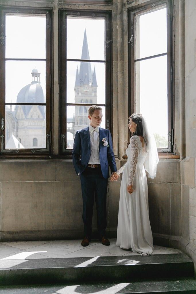 Hochzeitsfoto von Braut und Bräutigam vor einem Fenster   Foto: Hanna Witte
