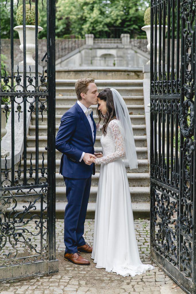 Hochzeitsfotoidee: Braut und Bräutigam stehen zwischen einem hohen Eisentor   Foto: Hanna Witte