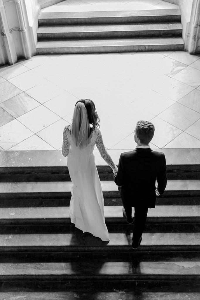 Hochzeitsfoto von oben: Braut und Bräutigam gehen Hand in Hand eine Treppe hinauf   Foto: Hanna Witte