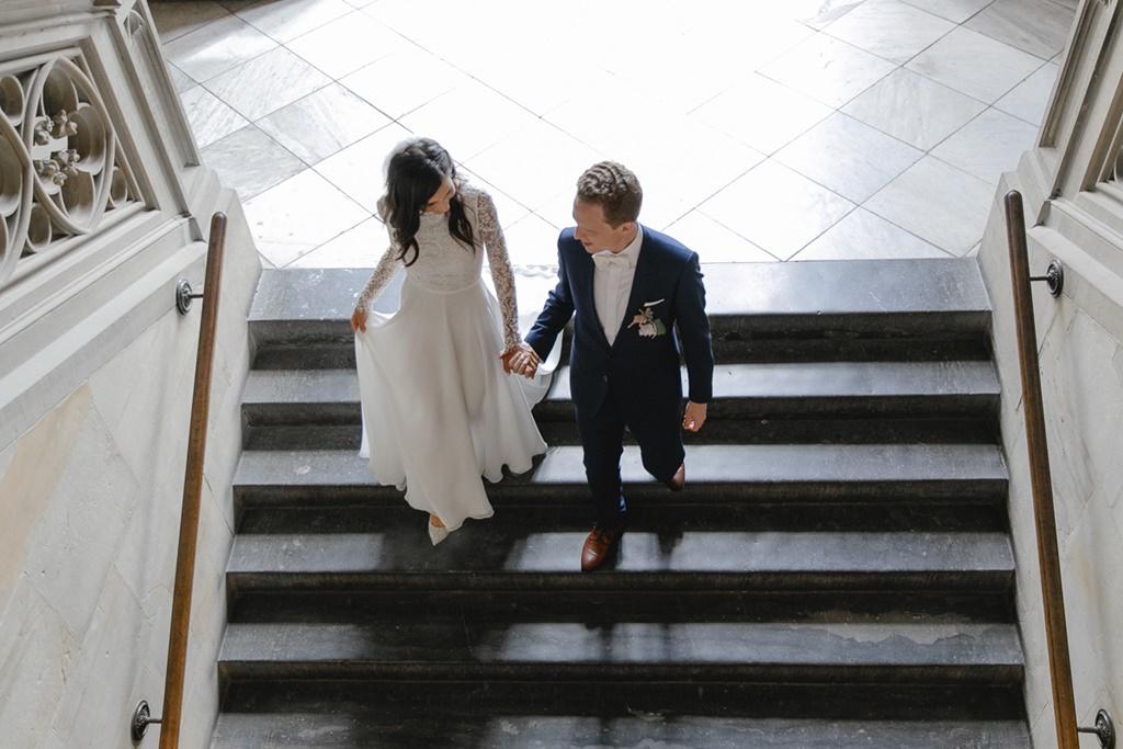 Hochzeitsfoto von oben: Braut und Bräutigam gehen Hand in Hand eine Treppe hinab   Foto: Hanna Witte