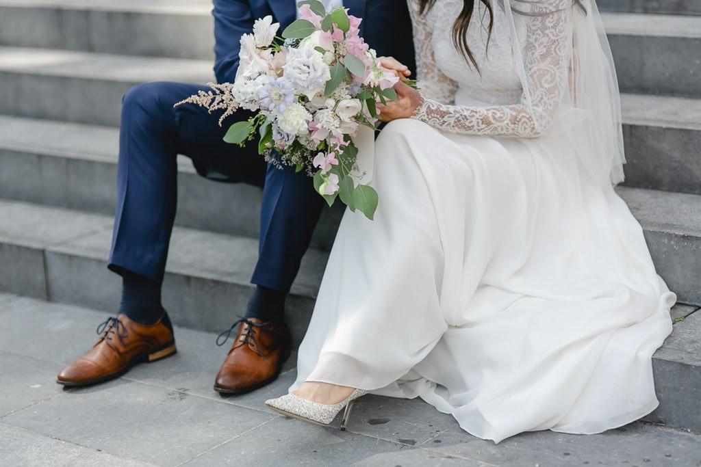originelle Paarfotoidee von Braut und Bräutigam mit Hochzeitsstrauß   Foto: Hanna Witte