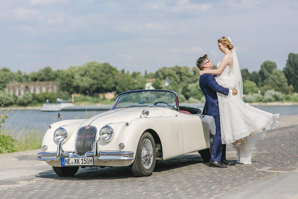 Für das Hochzeitsfoto posiert das Brautpaar mit einem Oldtimer | Foto: Hanna Witte