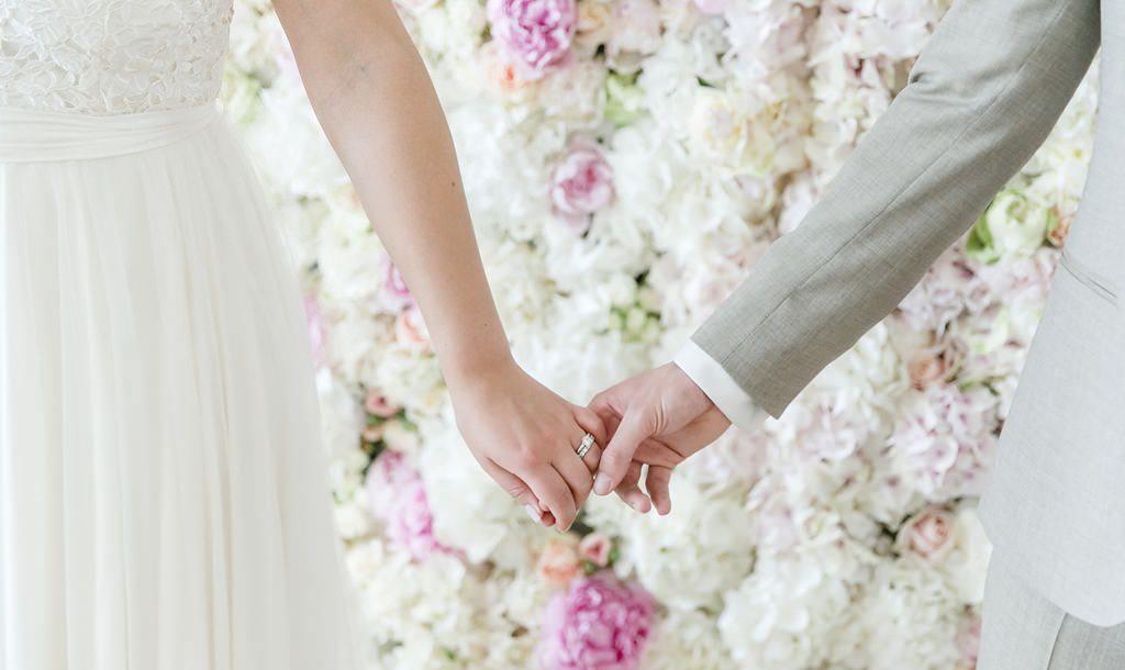 Braut und Bräutigam halten sich vor einer Flower Wall in Weiß und Rosa an den Händen | Foto: Hanna Witte