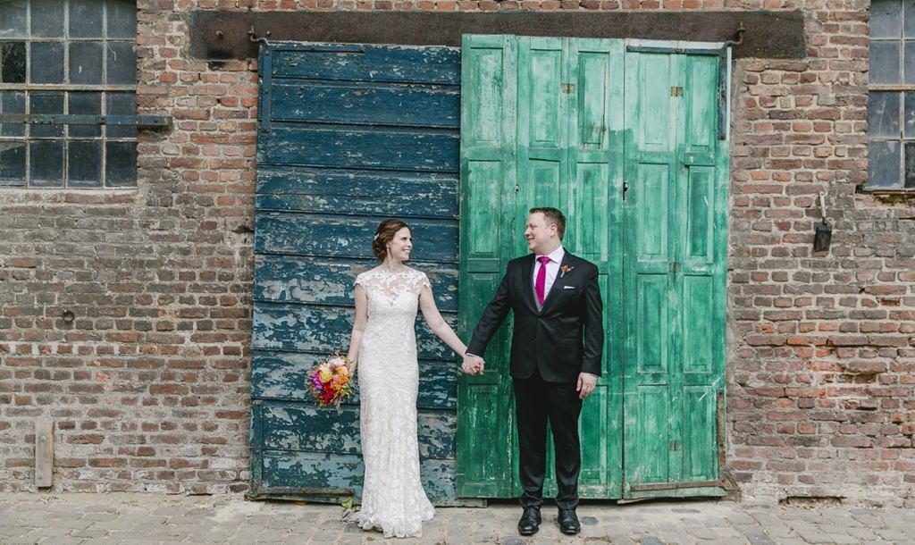 Paarfotoidee: Das Brautpaar posiert Hand in Hand vor einem alten Scheunentor | Foto: Hanna Witte