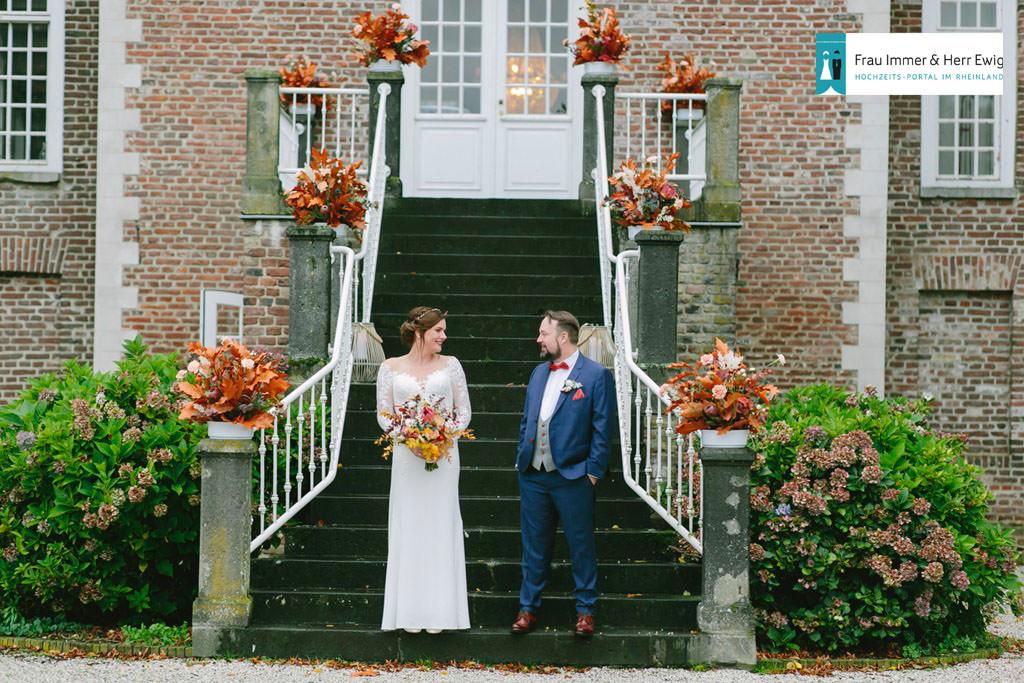 das Brautpaar steht auf einer herbstlich dekorierten Treppe von Schloss Hertefeld | Foto: Hanna Witte