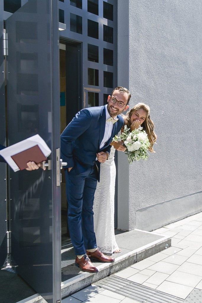das Brautpaar schaut aufgeregt aus der Tür des Standesamts | Foto: Hanna Witte