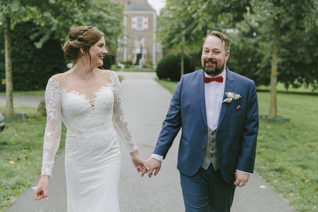 ungestelltes Hochzeitsfoto vom Brautpaar, das einen Weg entlang geht | Foto: Hanna Witte