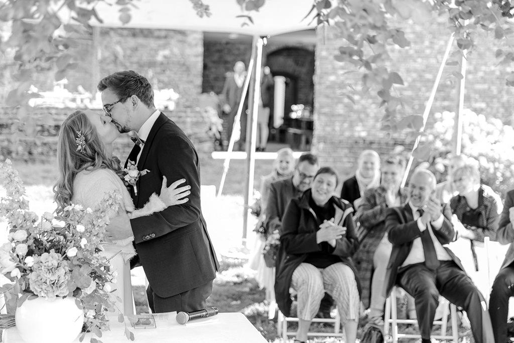 das Brautpaar küsst sich nach der Freien Trauung draußen | Foto: Hanna Witte