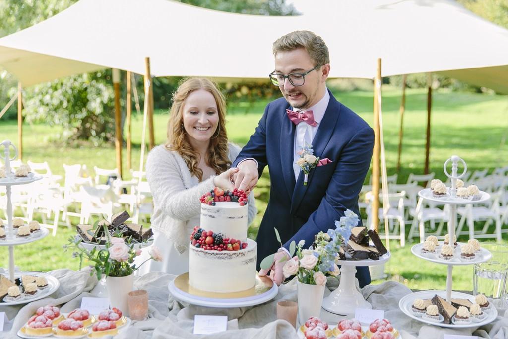 Das Brautpaar schneidet im Freien die Hochzeitstorte im Undone Look an | Foto: Hanna Witte