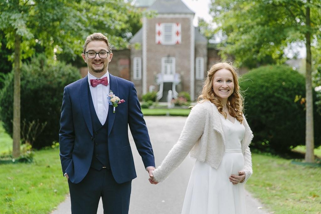 Hochzeitsfoto mit Babybauch: Der Bräutigam und die schwangere Braut halten sich an den Händen | Foto: Hanna Witte