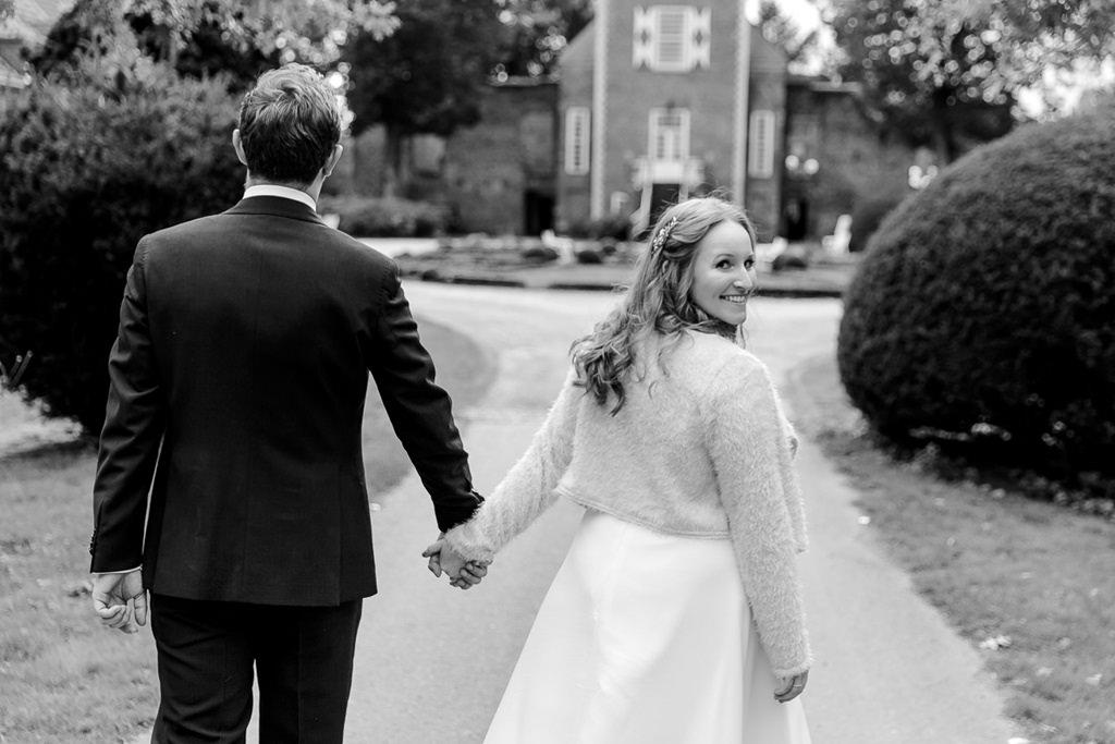 schwarz-weiß Hochzeitsfoto vom Brautpaar, das einen Weg entlang geht | Foto: Hanna Witte