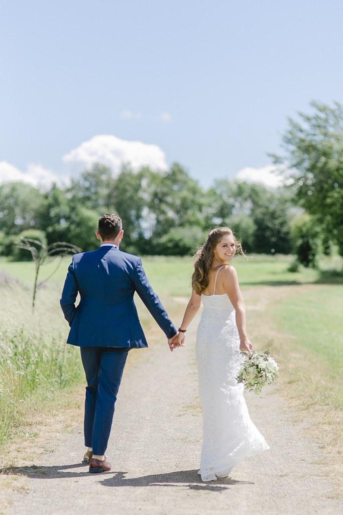 Hochzeitsfotoidee: Das Brautpaar läuft einen Weg entlang | Foto: Hanna Witte
