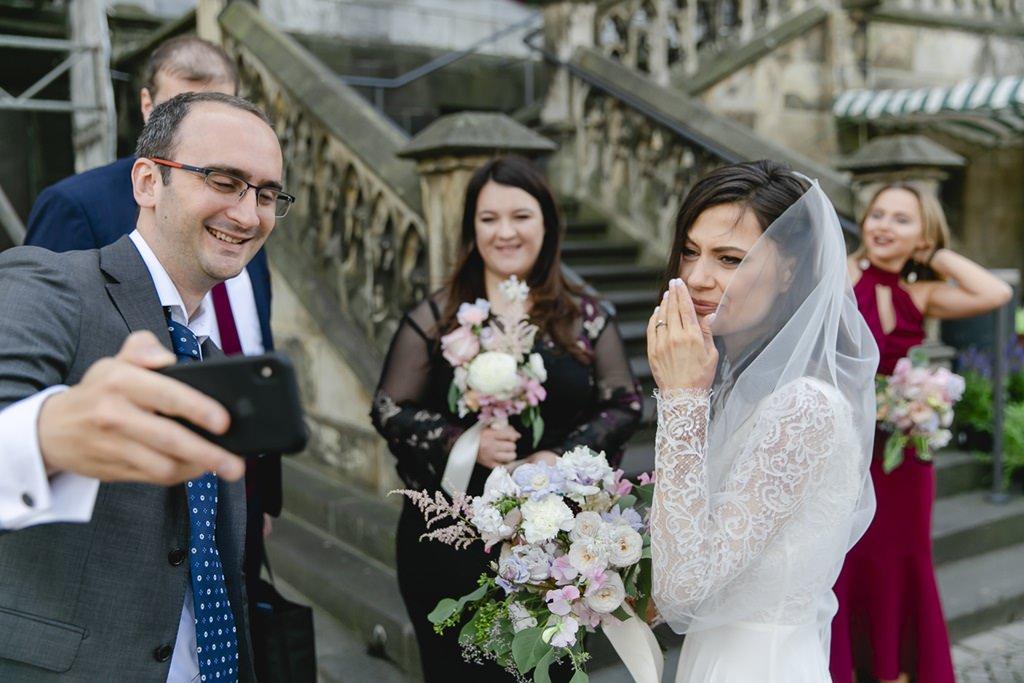 ein Gast zeigt der Braut ein Hochzeitsfoto auf dem Handy | Foto: Hanna Witte