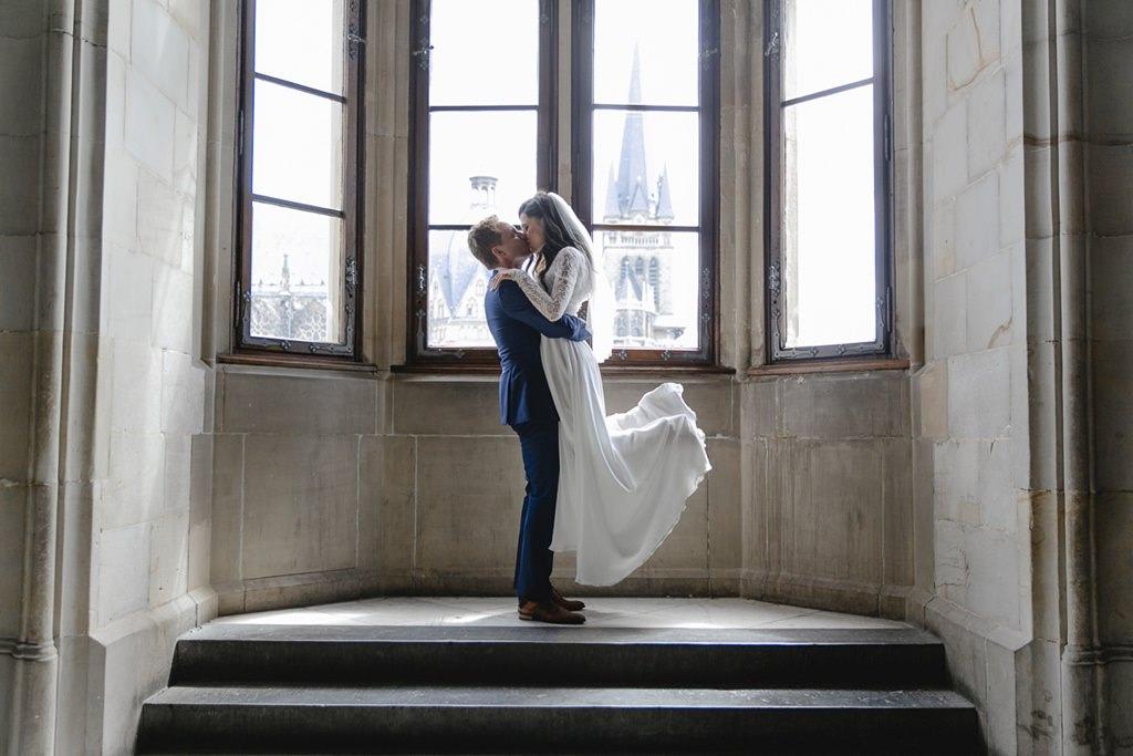 der Bräutigam hebt die Braut vor einem hohen Fenster hoch | Foto: Hanna Witte