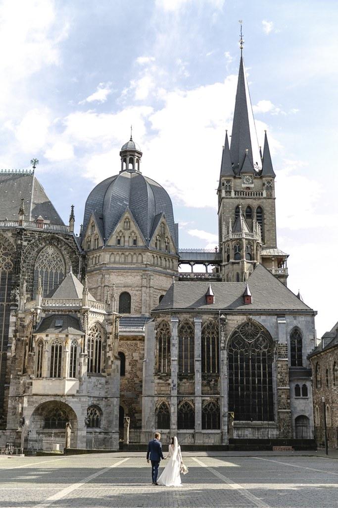 das Brautpaar läuft auf den Aachener Dom zu | Foto: Hanna Witte
