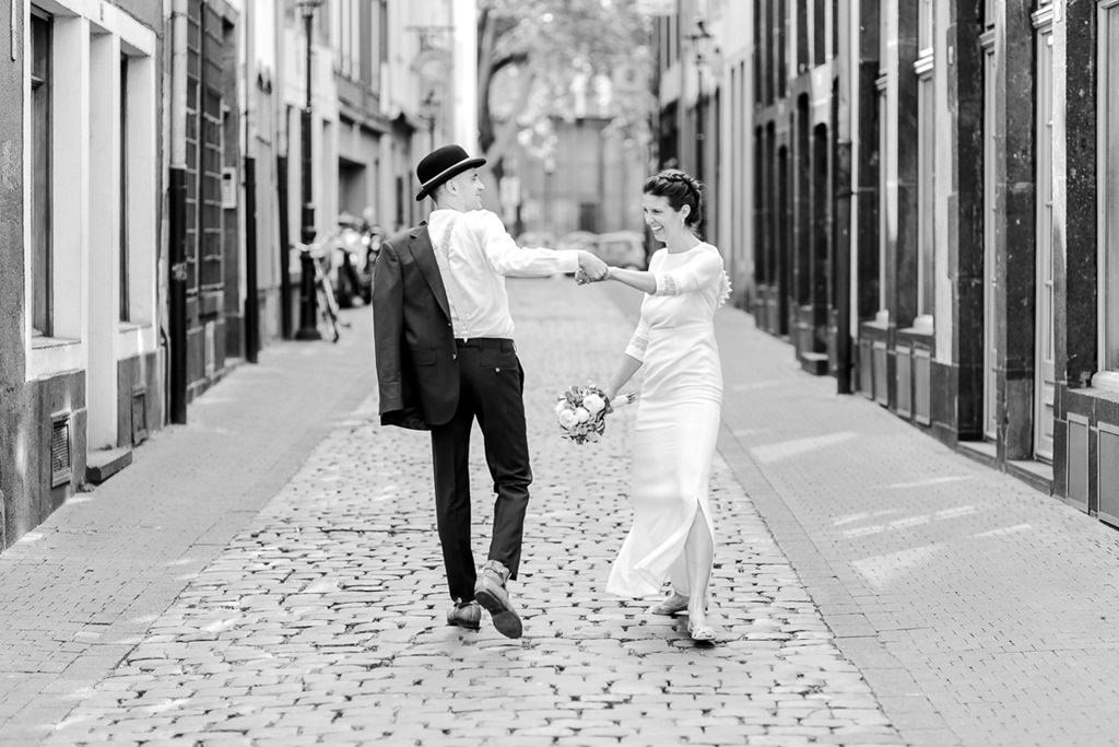 das Brautpaar läuft ausgelassen durch die Kölner Altstadt | Foto: Hanna Witte
